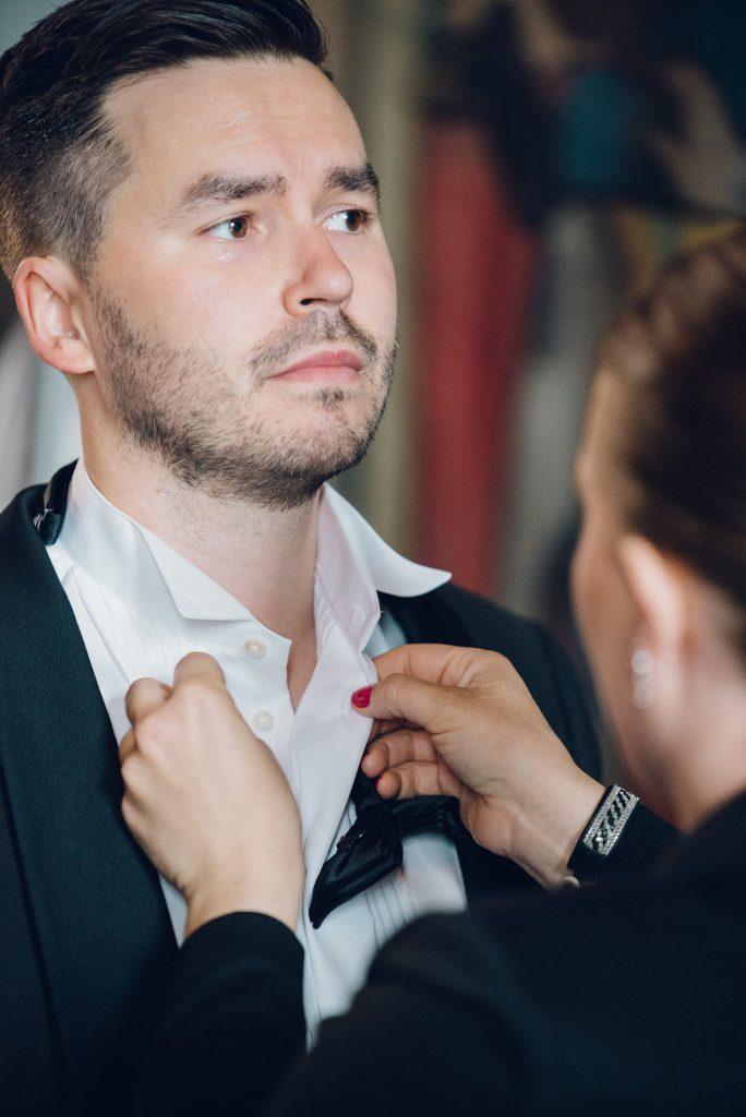 Andreas er brudgom. Moren hans knytter sløyfa hans så han er klar til vielsen. Bryllupsfotograf i Oslo er Hans Dalane-Hval