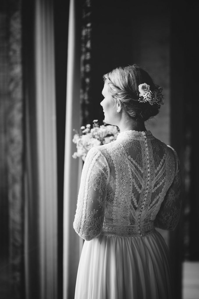 Brudgom Nora står i Rådhuset i Oslo. Hun har hvit brudekjole. Bryllupsfotograf er Hans Dalane-Hval