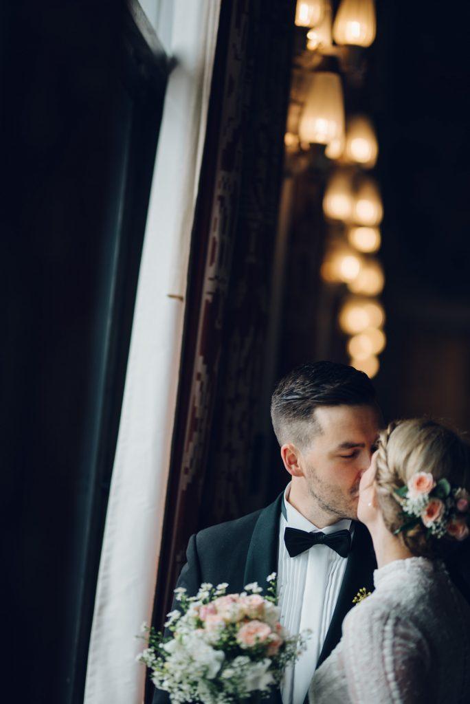 Brud og brudgom kysser hverandre. Vi ser brudebuketten. De står i rådhuset i Oslo.