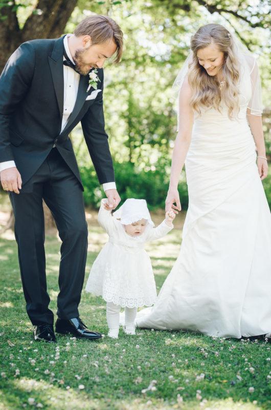 Brud og brudgom leier datteren sin. De tar bryllupsbilder i søndre park i Hønefoss