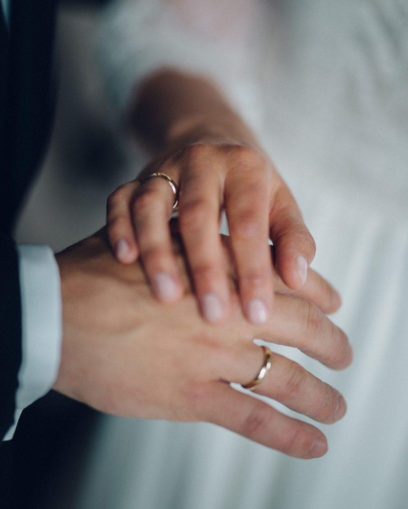Bryllupsfotograf i Oslo. Brud og brudgom holder hender og viser fram gifteringene sine.