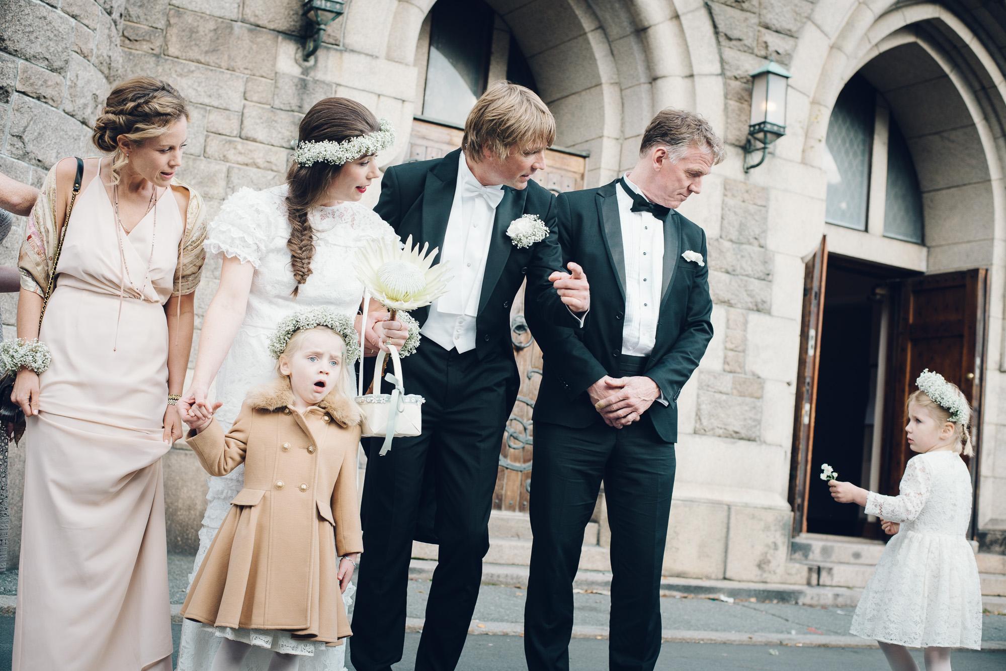 Brud og brudgom tar gruppebilde med forlovere og barn. Foran Fagerborg kirke.