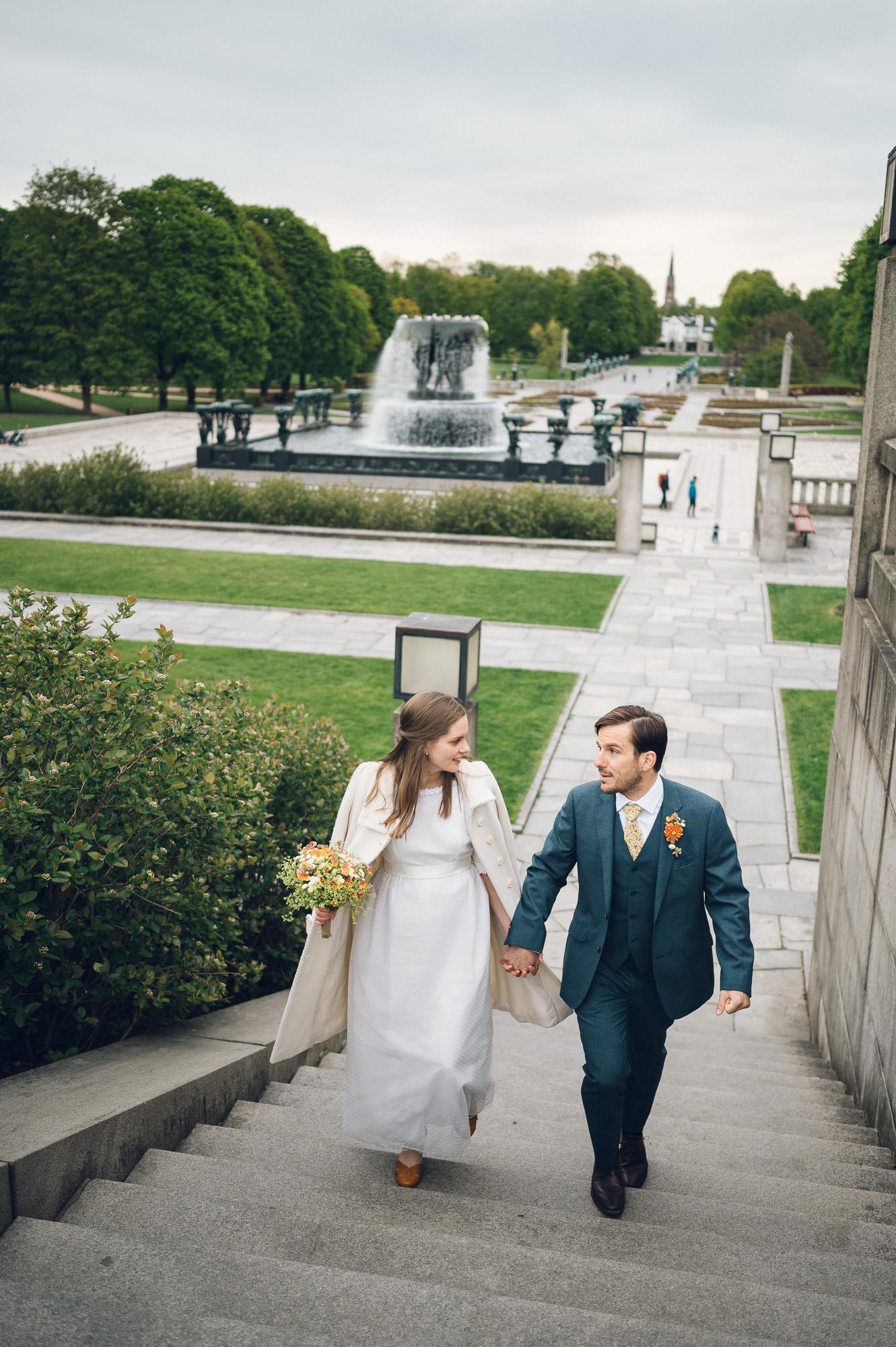 Bryllupsfoto av brud og brudgom. De går opp trappene i Frognerparken.