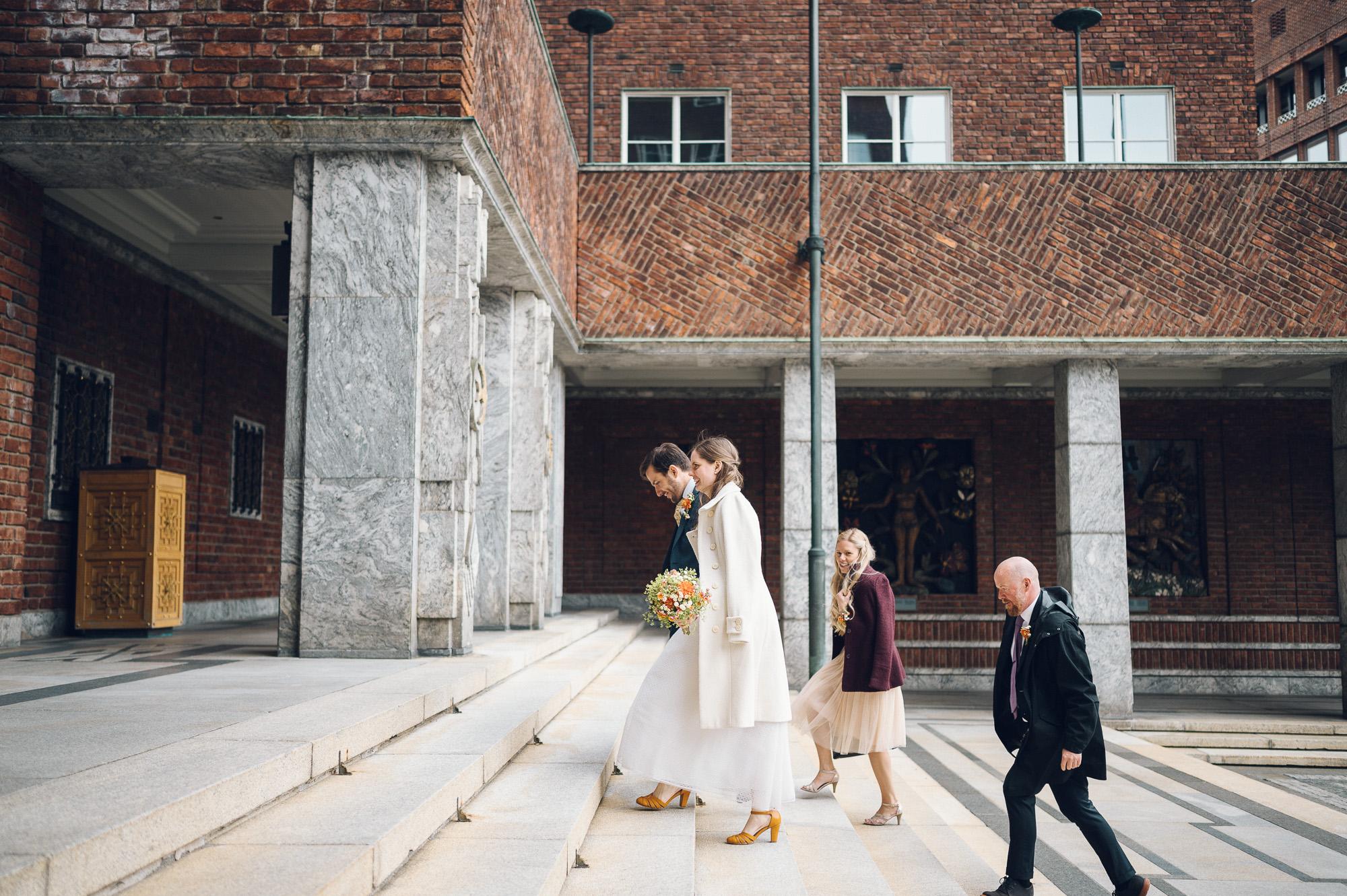 Bryllupsfoto av brud og brudgom som går opp trappa på rådhuset.
