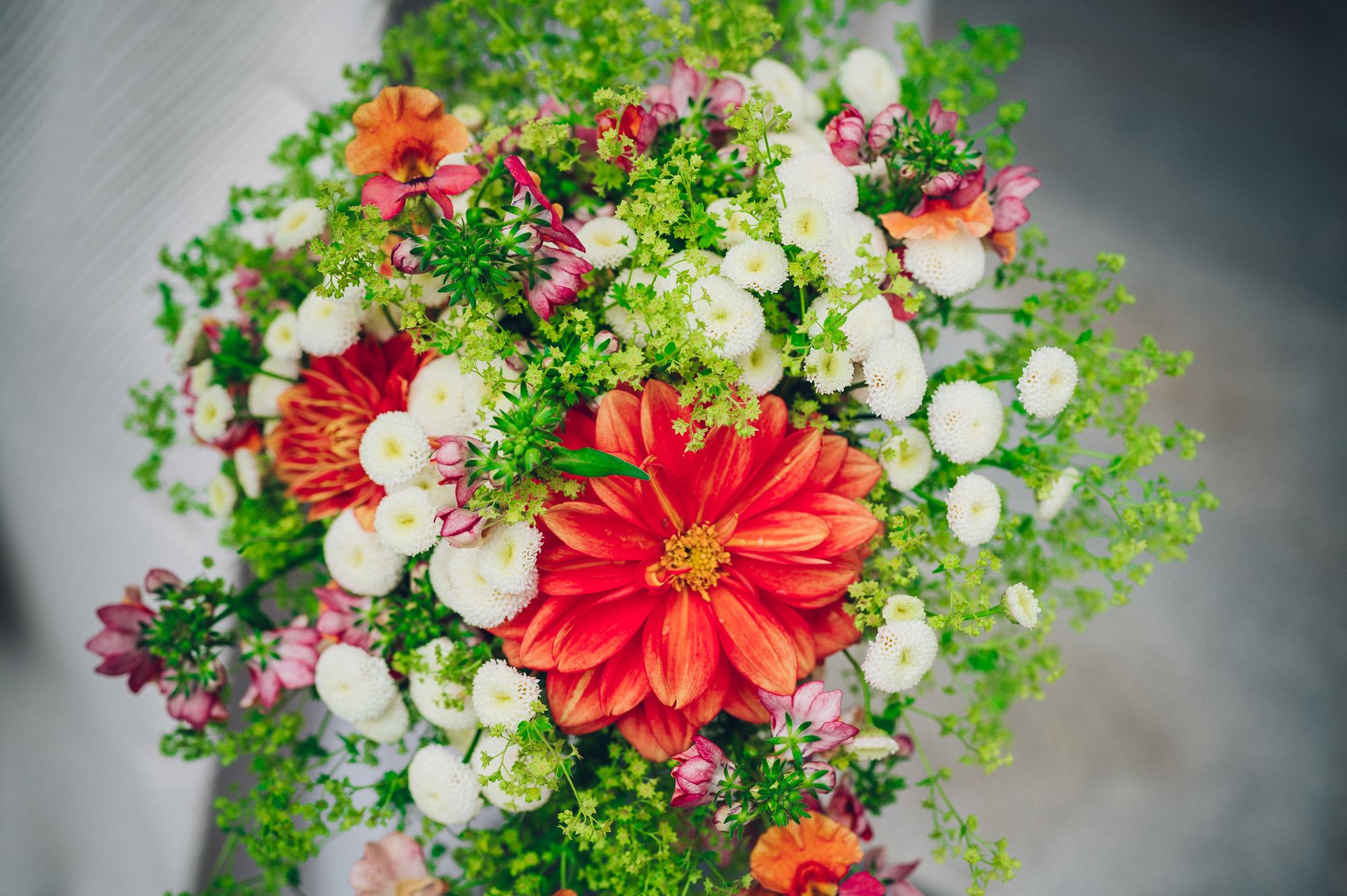 Nærbilde av bryllupsbuketten. Røde og grønne blomster.