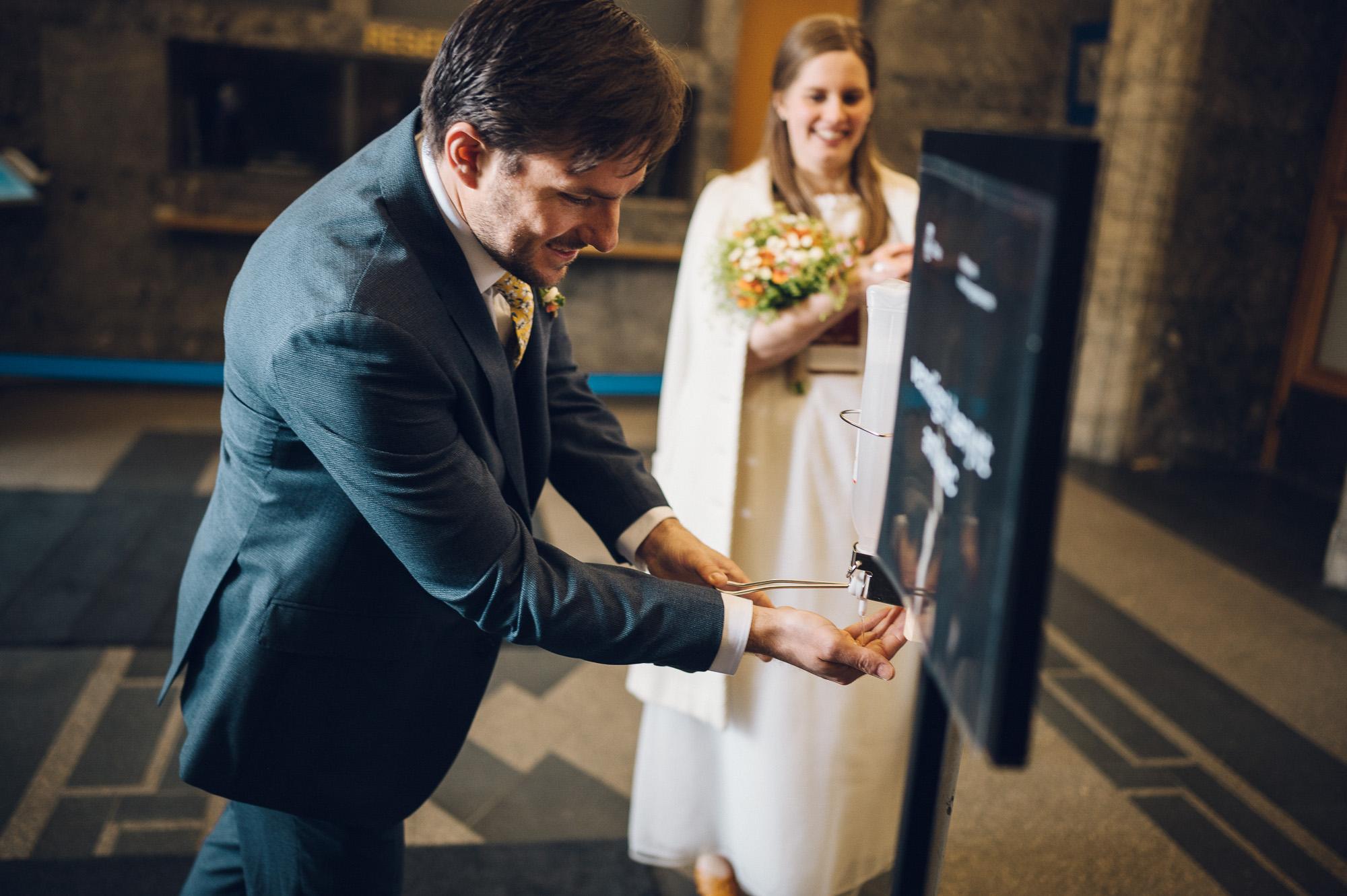 Brudgommen tar seg et sprut antibac. Bruden står i bakgrunnen og venter.