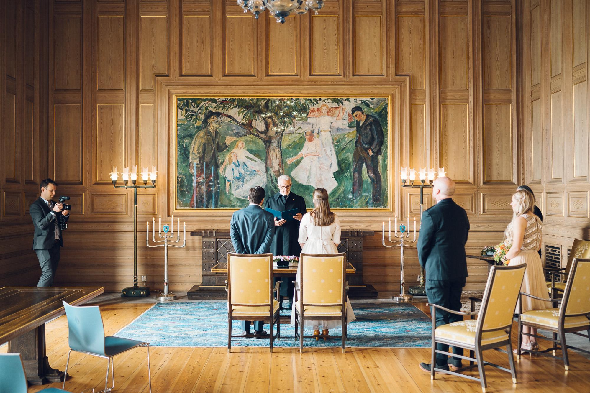 Vielse på rådhuset. Et maleri i bakgrunnen. Stor sal. Brud og brudgom står i midten av bildet.