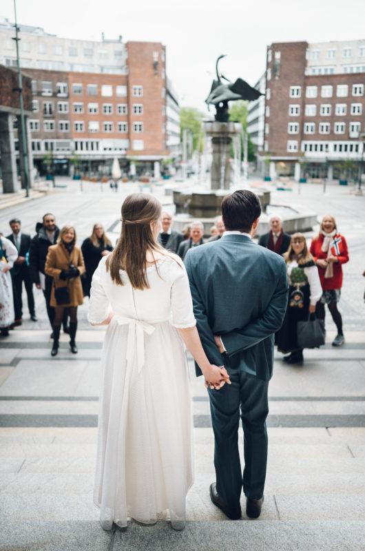Brud og brudgom står utenfor rådhuset og ser ut på alle som har møtt opp. De har nettopp giftet seg.