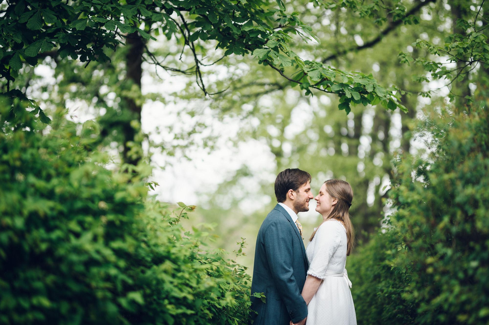Bryllupsfoto av brud og brudgom. De ler og stemningen er romantisk.